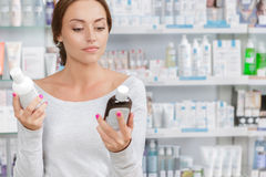Girl can't decide what to buy in drugstore Royalty Free Stock Photo
