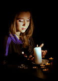 Girl with a candle. In a dark room stock photos
