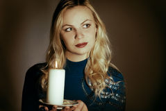 Girl with a candle. In a dark room royalty free stock image