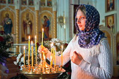 Girl with a candle. Girl with a candle in the Orthodox Church Stock Images