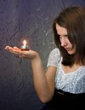 Girl with candle. Closeup photo of the brunette with candle on dark blue background Stock Photos