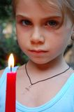 Girl with candle. Little serious girl with a cross on her chest holding a burning candle Royalty Free Stock Image