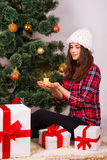 Girl with a candle and gifts under the Christmas tree Royalty Free Stock Image