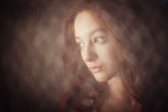The girl in the candlelight. Sweet girl with curly hair sensual look aside by candlelight Stock Image