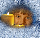 Girl with candles looking through a frosted window Royalty Free Stock Photos