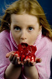 Girl with candy. Girl is eating cherry bonbons stock image