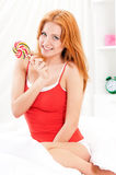 Girl with candy in bedroom Stock Photography