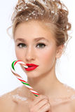 Girl with candy cane. Portrait of young beautiful girl with stylish make-up and hairdo, candy cane and snowflakes in her hair stock photography