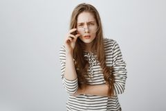 Girl cannot see clearly without glasses. Cute young teenager squinting and frowning, having bad vision, taking off royalty free stock images