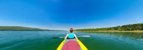 Girl in a canoe floating down the river. Royalty Free Stock Photo