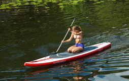 Girl in canoe paddling on a canal in the city Stock Images