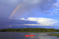 Girl canoeing. Woman canoeing in a beautiful lake with rainbow in the sky royalty free stock image