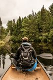 Girl canoeing with Canoe on the lake of two rivers in the algonquin national park in Ontario Canada on cloudy day Stock Photos