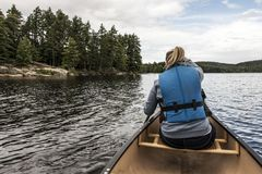 Girl canoeing with Canoe on the lake of two rivers in the algonquin national park in Ontario Canada on sunny cloudy day Royalty Free Stock Photography