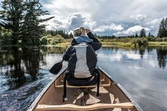 Girl canoeing with Canoe on the lake of two rivers in the algonquin national park in Ontario Canada on sunny cloudy day Royalty Free Stock Image