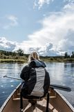 Girl canoeing with Canoe on the lake of two rivers in the algonquin national park in Ontario Canada on sunny cloudy day Royalty Free Stock Images