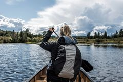 Girl canoeing with Canoe on the lake of two rivers in the algonquin national park in Ontario Canada on sunny cloudy day Royalty Free Stock Photo