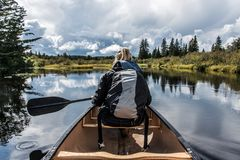 Girl canoeing with Canoe on the lake of two rivers in the algonquin national park in Ontario Canada on sunny cloudy day Royalty Free Stock Photos