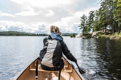 Girl canoeing with Canoe on the lake of two rivers in the algonquin national park in Ontario Canada on sunny cloudy day Stock Images