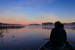 Girl Canoing at Sunrise. Thoughtful girl looking out to sunrise on Lake Muskoka Royalty Free Stock Photos