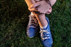 Girl in canvas trainers sitting cross legged on green grass stock photography