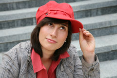 Girl in a cap. Portrait of the young girl in a red cap against steps Stock Image