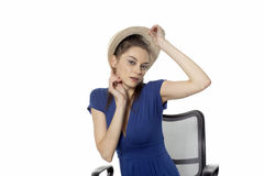 Girl and cap. Babe sitting chair and fitting straw cap Stock Photography