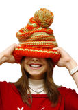 Girl and a cap. The Image of the girl putting on a knitted cap Stock Image