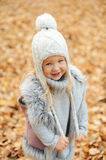 Girl in a cap and autumn leaves standing in autumn park in the evening. Girl in a cute cap and autumn leaves standing in autumn park in the evening Stock Image