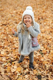 Girl in a cap and autumn leaves standing in autumn park in the evening. Girl in a cute cap and autumn leaves standing in autumn park in the evening Royalty Free Stock Images