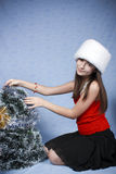 Girl in a cap with the Christmas decorations. Stock Photography