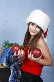Girl in a cap with the Christmas decorations. Royalty Free Stock Image