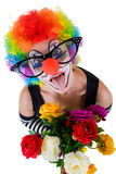Girl in cap and clown costume with a bouquet of flowers puts out the tongue looks up Royalty Free Stock Photos