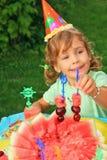 Girl in cap eats fruit in garden,happy birthday royalty free stock photos