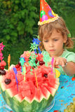 Girl in cap eats fruit, happy birthday Royalty Free Stock Photo
