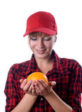 Girl in a cap holding an orange Stock Images