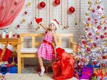 Girl in a cap and mittens of Santa Claus dancing around the bag with Christmas gifts Stock Photo