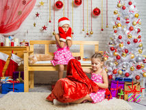 Girl in a cap and mittens of Santa Claus saw that bag climbs another girl Royalty Free Stock Photos