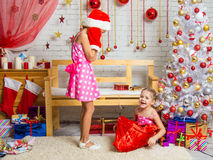 Girl in a cap and mittens of Santa Claus was very surprised that out of the bag got out another girl Stock Photo