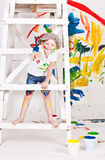 Girl in a cap with paints Royalty Free Stock Photography