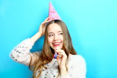 Girl in a cap and with a pipe. Beautiful girl in a cap and with a pipe on a blue background. Concept birthday Stock Photo