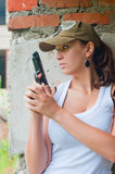 The girl in a cap with a pistol hides about a wall Royalty Free Stock Images