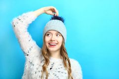 Girl in a cap with a pompon. Beautiful smiling girl in a soft sweater and a cap with a pompon on a blue background Stock Photos