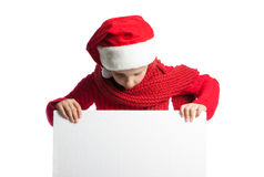 Girl in a cap of Santa Claus looking at a poster Royalty Free Stock Image