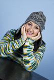Girl with cap smiling at table Royalty Free Stock Images