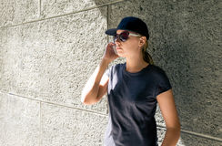 The girl in a cap speaks by phone royalty free stock photo