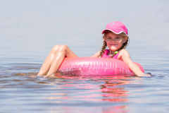 The girl in the cap swim in river sat on the lap swimming and looked into the frame Royalty Free Stock Images
