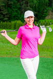 Girl in a cap and a T-shirt with a golf club. Outdoors Royalty Free Stock Image