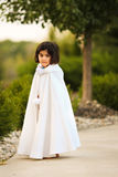 Girl in cape. Little girl in white cape outdoors royalty free stock image