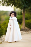 Girl in cape. Little girl in white cape outdoors Royalty Free Stock Photos